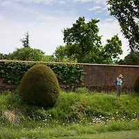 Helmingham Hall gardens in Suffolk England. With woman looking into the moated walled garden