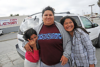 From left, Iris Garcia, 11, Estela Cardenas, and Brisa Garcia, 12, by their car as they wait for the warming shelter at 20 W. Market St. in Salinas to open.