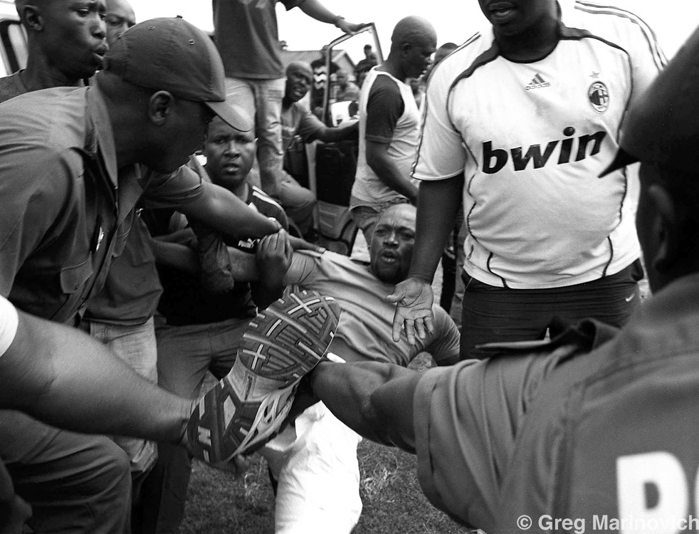 A resident resists arrest by police, Sharpeville, Gauteng, South Africa February 23, 2010. residents of this township in the Vaal, south of Johannesburg were protesting corruption and nepotism, and allegedly burnt a local official's house and car. Photo Greg Marinovich.