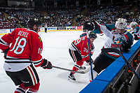 KELOWNA, CANADA - APRIL 7: Matt Revel #18 and Colton Veloso #39 of the Portland Winterhawks check Nolan Foote #29 of the Kelowna Rockets into the boards in front of the bench on April 7, 2017 at Prospera Place in Kelowna, British Columbia, Canada.  (Photo by Marissa Baecker/Shoot the Breeze)  *** Local Caption ***