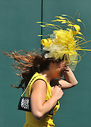 © licensed to London News Pictures. EPSOM, UK.  03/06/11. A race goer holds onto her hat as the wind takes hold.  Epsom Derby Ladies Day. Sunshine and wind made for a busy Ladies Day today, 3rd June 2011.  Photo credit should read Stephen Simpson/LNP