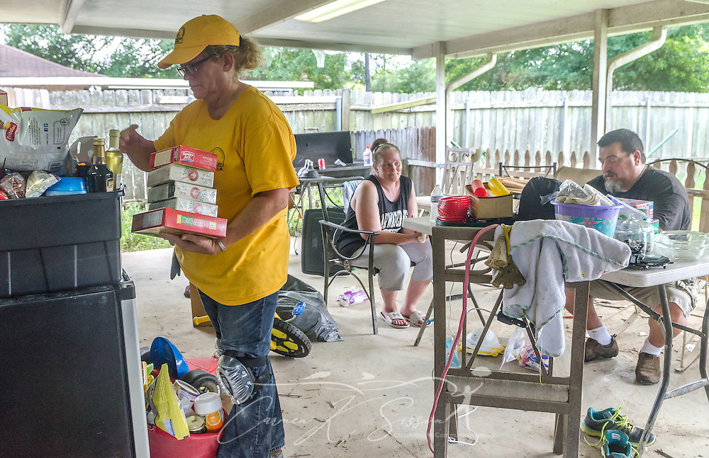 Southern Baptist Disaster Relief volunteer Kim Rowland, a member of East Dublin Dayspring Worship Center in East Dublin, Ga., stacks salvageable food in boxes as homeowners Karen Johnson and Phillip Carpenter, of Immaculate Conception Church, take a break from cleanup,  Aug. 26, 2016, in Denham Springs, La. Rowland, along with other SBDR Georgia volunteers, is at the couple's home this week, helping them mud out their flood-damaged house. They are among thousands of Louisiana residents affected by a mid-August flood. (Photo by Carmen K. Sisson)