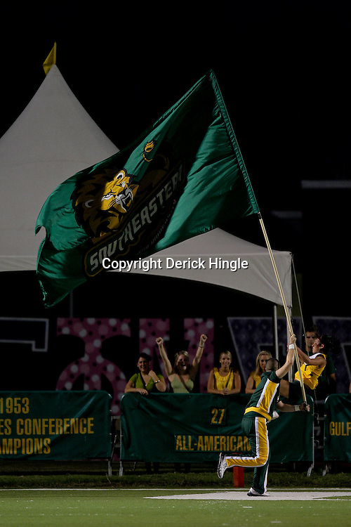 10 September 2009: A Southeastern Louisiana Lions cheerleader runs with the flag after a score during a game between Southeastern Louisiana University Lions and Union College at Strawberry Stadium in Hammond, Louisiana.