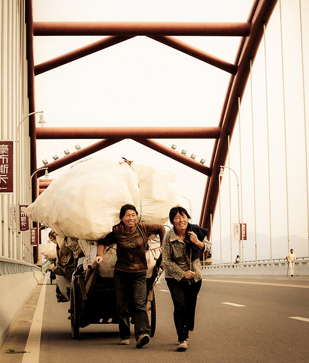 two women pulling cart across bridge