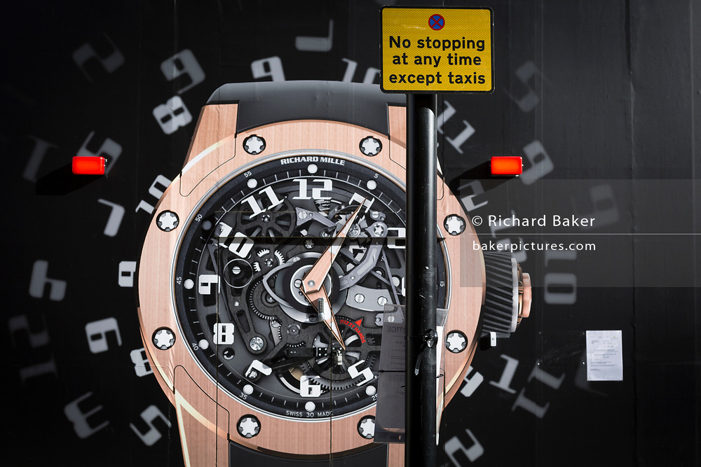 The construction hoarding of a watch and a notice for parking times outside the new Richard Mille shop in Bond Street, on 19th February 2019, in London, England.