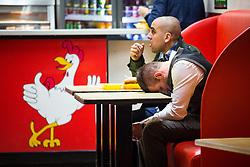 "© Licensed to London News Pictures . 19/12/2015 . Manchester , UK . A man slouched forward at a fast food chicken restaurant . Revellers in Manchester enjoy "" Mad Friday "" - also known as "" Black Eye Friday "" - the day on which emergency services in Britain are typically at their busiest , as people head out for parties and drinks to celebrate Christmas . Photo credit : Joel Goodman/LNP"