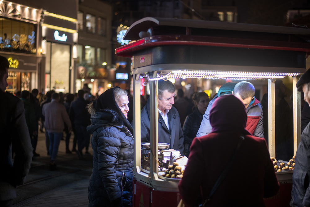 People gather around food cart on the busy streets of Istanbul, Turkey as they wait for roasted chestnuts