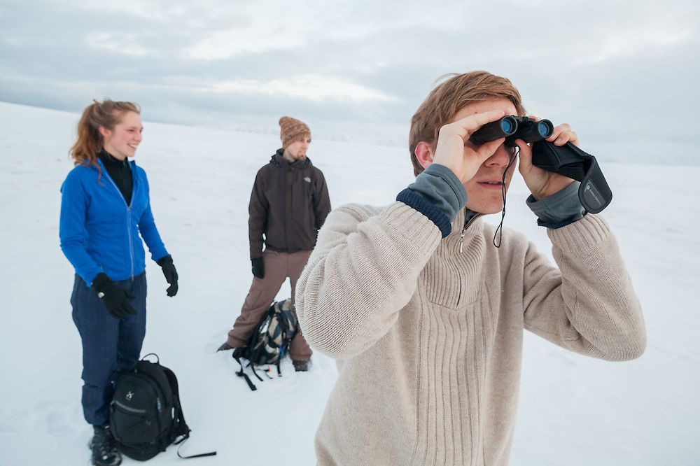 Robin de Vries (hiking with Sofie Vej Ugelvig, left, and Alexander Lohse) looks through his binoculars on a hike across Sverdruphamaren, Svalbard.
