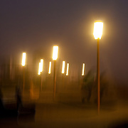 Blurred scene of pedestrian path at night.