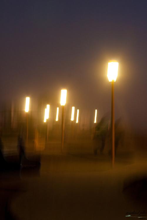 Blurred scene of pedestrian path at night.
