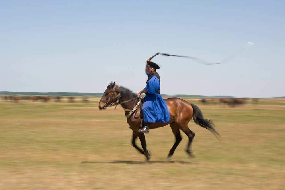 Typical Hungarian herdsman's riding ritual with a whip, Hortobagy National Park, Hungary