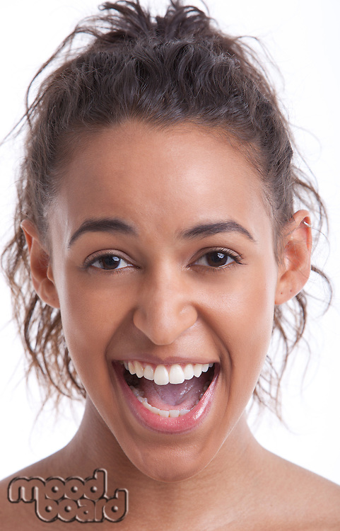 Portrait of young Mixed Race woman laughing against white background