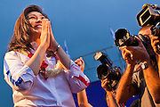 "01 JULY 2011 - BANGKOK, THAILAND:  YINGLUCK SHINAWATRA, leader of the Pheua Thai party, ""wais"" a traditional Thai greeting to voters at the last Pheua Thai rally of the year in Bangkok Friday. Thailand's divisive election campaign drew to a close Friday in Bangkok. Most of the parties had large rallies in an effort to sway last minute undecided voters. Pheua Thai, the party of ousted Prime Minister Thaksin Shinawatra held a massive rally in Rajamakala Stadium (also called Ramkamhaeng Stadium) to close out their campaign. A monsoon thunderstorm didn't keep people away from the event. Most Thai public opinion polls show Pheua Thai with a healthy lead over their arch rivals (and incumbent party in power) the Democrats. Thaksin's youngest sister, Yingluck Shinawatra, is running for Prime Minister under the Pheua Thai banner. If elected, she will be Thailand's first female Prime Minister.      PHOTO BY JACK KURTZ"