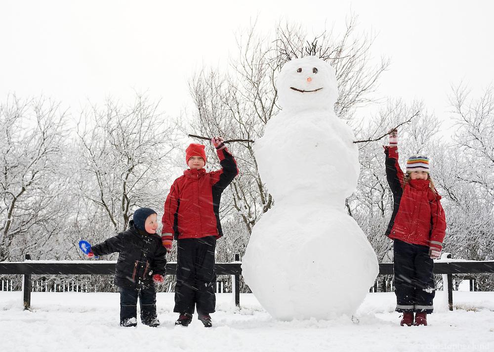 Proud group of kids in winterclothes standing by their snowman. Snow falling on ground. Trees in background...Krakkarnir stolltir við stóran snjókarl sem þau gerðu ásamt pabba.
