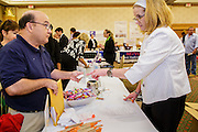30 JULY 2012 - PHOENIX, AZ:  DAVID MENDOZA (left) accepts a business card from BETSY LILLEY, a recruiter at Consumer Cellular at the Phoenix Job Fair in Phoenix, AZ. Lilley said Consumer Cellular hires 30 customer service representatives a month. The job fair was sponsored by National Career Fairs, which organizes job fairs across the US. Several hundred people attended the job fair, with some arriving hours before it started. More than 30 employers and prospective employers were conducting interviews at the job fair. There were also resume coaches and educational institutions on site. Arizona is still grappling with the recession. The state's unemployment rate is stuck at 8.2% and the Phoenix metropolitan area has one of the highest home foreclosure rates in the United States.     PHOTO BY JACK KURTZ