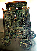 Bronzed wheeled stand with an animal frieze on the ring and figures in the side panels.  Made in Cyprus, 13th or 12th century BC.  The panels principally show ; a seated harp-player approached by a musician and a serving boy; a winged sphinx, a lion gripping a water by its neck, and a chariot.