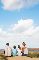 Family sitting on sand dune on beach looking at view back view