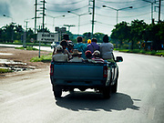 05 JULY 2017 - SA KAEO, THAILAND:  Cambodian migrant workers in Sa Kaeo, Thailand, riding in the back of a pickup truck drive toward the Thai-Cambodian border. The Thai government proposed new rules for foreign workers recently. The new rules include fines of between 400,000 and 800,00 Thai Baht ($12,000 - $24,000 US) and jail sentences of up to five years for illegal workers and people who hire illegal workers. Hundreds of companies fired their Cambodian and Burmese workers and tens of thousands of workers left Thailand to return to their countries of origin. Employers and human rights activists complained about the severity of the punishment and sudden implementation of the rules. On Tuesday, 4 July, the Thai government suspended the new rules for 180 days and the Cambodian and Myanmar governments urged their citizens to stay in Thailand, but the exodus of workers continued through Wednesday.    PHOTO BY JACK KURTZ