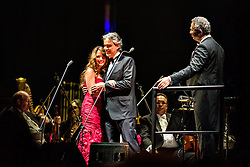 ANAHEIM, CA - JUN 9: Italian tenor Andre Bocelli performed Granada, New York, La Boheme, LaTraviata among others keeping audience mesmerized at the Honda Center in Anaheim, CA. The magical night included producer David Foster on Piano, Violinist Caroline Campbell, American Idol Season 3 winner Soul Singer Fantasia, Cuban Soprano Maria Aleida and Orchestra Conductor Eugene Kohn. Italian tenor Andrea Bocelli embraces Cuban soprano Maria Aleida after performin together on stage. While Conductor Eugene Kohn (R) looks upon. All fees must be ageed prior to publication, Byline and/or web usage link must  read  PHOTO: SilvexPhoto.com