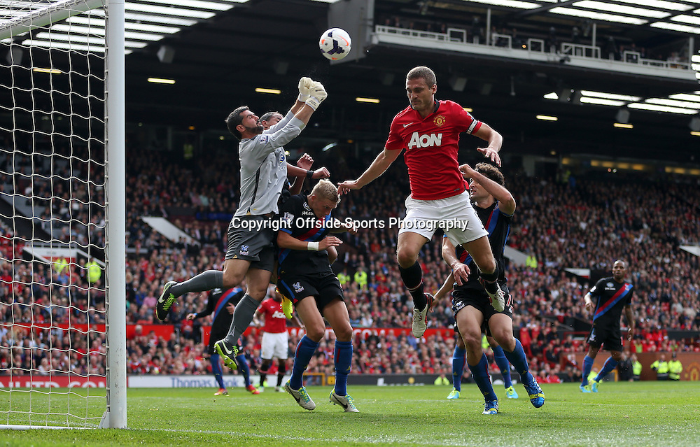 14th September 2013 - Barclays Premier League - Manchester United v Crystal Palace - Nemanja Vidic of Man Utd jumps as Palace goalkeeper Julian Speroni punches clear - Photo: Simon Stacpoole / Offside.
