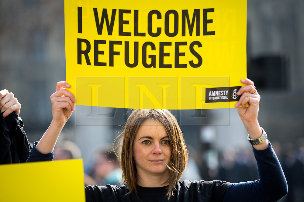"""© Licensed to London News Pictures. 16/03/2017. London, UK. Activists from Amnesty International UK hold a """"flashmob"""" demonstration in Westminster today, protesting against Donald Trump's travel ban executive order. Yesterday, a federal judge in Hawaii blocked President Donald Trump's travel ban, shortly before it was to be put in place. Photo credit : Tom Nicholson/LNP"""