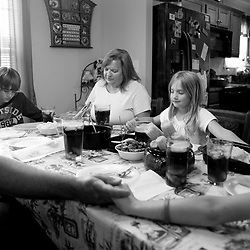 Kyle Green | The Roanoke Times<br /> 5/11/2012 The Shupe family (left to right) Jeff, Seth (age 12), Wendy, Makenzi (age 7), and Cassie (age 11 ) pray together before dinner at their house in Fincastle, Virginia. Salem educators Jeff and Wendy Shupe wed in 2010. It was a second marriage for each of them. Between the couple, there are six children, ages 7 to 25. But that wasn't Brady-Bunch-enough. The couple decided to adopt and their international search led them to two children with special needs from Bulgaria. The adoptions won&Otilde;t be finalized until later this summer, but the Shupes visited Caden, who has Down syndrome, and Avery, who has dwarfism, over spring break. Now the couple needs to raise $10,000 in the next fourth months to bring the kids home.
