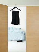 Dress on hanger in doorway of bedroom