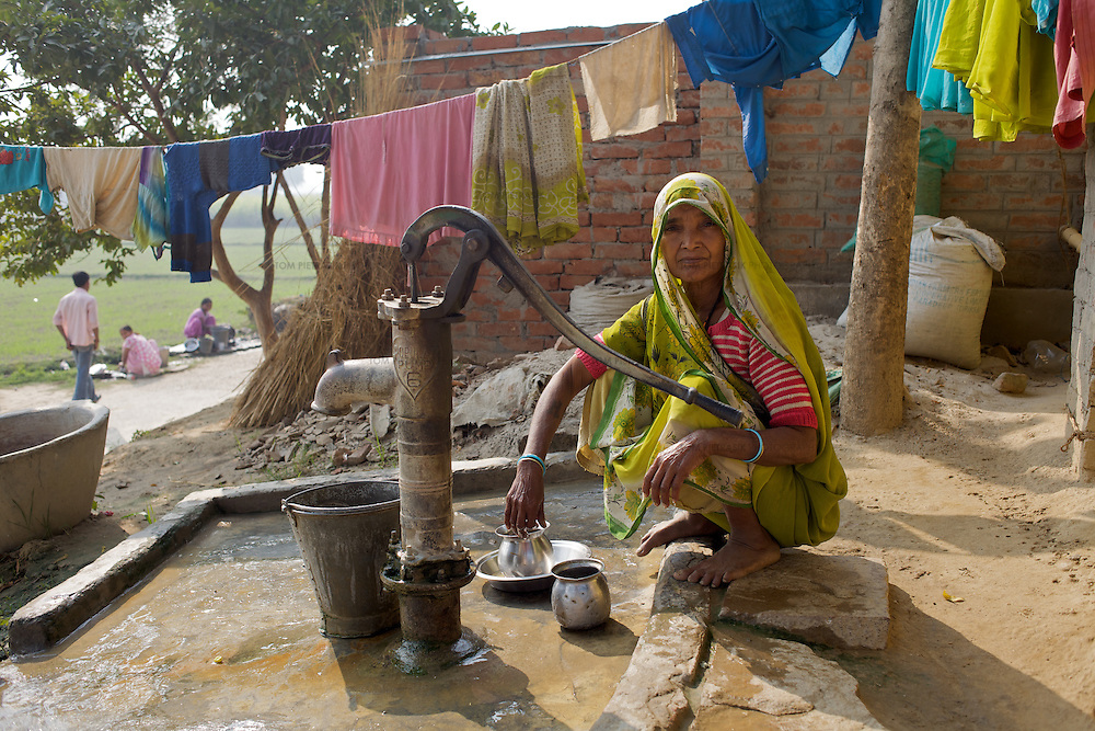 A woman washes clothes at a water pump in Madhopur village in Varanasi District. Most of the households in Madhopur village boast their own deep-pan toilet. This deep pan requires less water per flush and therefor avoids saturating the leeching pit, giving the latrine a longer life and avoiding contamination. ..UNICEF and the Uttar Pradesh Government, have identified 100 model Gram Panchayats (local-level village administration) in Varanasi District (out of a total of 702). The promotion of good sanitation and hygiene practices in these Gram Panchayats allows them to serve as examples for the remaining areas of the district to emulate. The promotion of hygiene and sanitation includes the construction and painting of school toilet blocks, the construction of individual toilets in households, the digging of garbage pits, recycling waste water and encouraging personal hygiene awareness. ..Only 32 percent of those living in Uttar Pradesh, India's largest state, have access to a toilet. Uttar Pradesh faces many challenges in it's efforts to address this deficiency. UNICEF supports the Uttar Pradesh government's sanitation and hygiene project at both the state and district levels. UNICEF is working to increase the capacity of all of those involved in the sanitation and hygiene project from state-level administrators through to Panchayati Raj (local-level administration) officers and influential individuals, including teachers, who live among rural communities. UNICEF has prioritised the need to communicate the importance of good sanitation and hygiene practice to these communities. The Uttar Pradesh government and UNICEF have focussed their campaign on eight districts (including Varanasi) with the intention that these serve as models for the remaining 62 districts of the state. UNICEF have identified areas of shortcoming within the government program and proposed solutions. These solutions include the proper training of masons, the provision of rural pans (toilet bowls wh