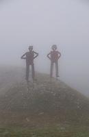 Naive metal swiss figures on a foggy hillside.
