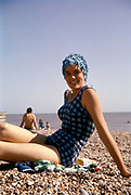 Girl wearing checked swimming costume ( bathing suit ) and 'Hedgehog' swimming cap' on a pebble beach UK 1961