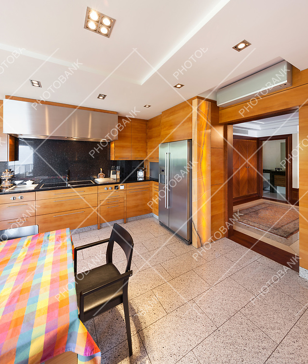 Interior of a modern apartment, wide domestic kitchen, wooden cabinet