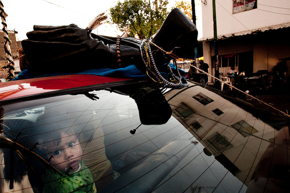 An infant and her family arrive to have their Sante Muerte Satute blessed at the shrine in Tipito, Mexico City,