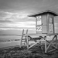 Black and white photo of Newport Beach CA lifeguard tower 22 at sunrise along the Pacific Ocean. Balboa Peninsula is a popular area of Newport Beach in Orange County Southern California USA. Copyright ⓒ Paul Velgos with All Rights Reserved.