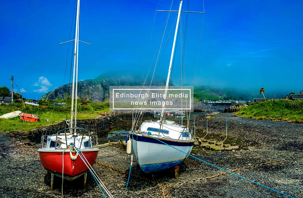 Yauchts tied up beside the tiny harbour on Easdale Island with Seil Island shrouded in low cloud in the background.  Easdale Island, the smallest permanently-inhabited island of the Inner Hebrides, Scotland<br /> <br /> (c) Andrew Wilson | Edinburgh Elite media