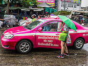 30 MAY 2013 - BANGKOK, THAILAND:   A woman negotiates with a taxi driver in the rain on Krung Kasem Rd in Bobae Market in Bangkok. Bobae Market is a 30 year old famous for fashion wholesale and is now very popular with exporters from around the world. Bobae Tower is next to the market and  advertises itself as having 1,300 stalls under one roof and claims to be the largest garment wholesale center in Thailand.   PHOTO BY JACK KURTZ