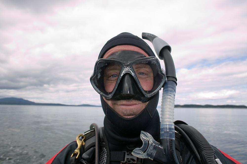 USA, Washington, Anacortes, (MR) Portrait of photographer Paul Souders wearing scuba goggles, snorkel and drysuit before diving in San Juan Islands.