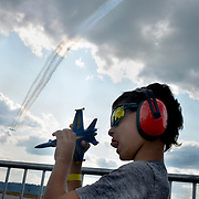 BRUNSWICK Maine- 8/26/17 -- Cristian Pedersen, 6, of Cheshire, Conn. plays with a toy jet as the U.S. Navy Blue Angels demonstration team flies overhead at Brunswick Landing on Saturday. The Blue Angels flew over Brunswick Landing as part of the Great State of Maine Airshow this weekend. Officials estimated that over 100,000 people enjoyed the show from inside and outside the gates. There were more static displays than there were in 2015's show and officials concluded not was a larger draw than in previous years.  Photo by Roger S. Duncan for The Forecaster.