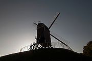 A windmill is silhouetted at sunset in Bruge, Belgium.