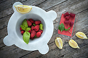 Mortar with fresh raspberries, basil leaves and lemon slices, above shot.