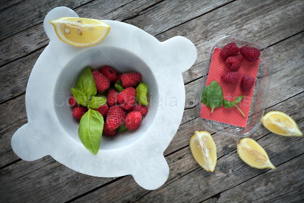 Mortar with fresh raspberries, basil leaves and lemon slices, above shot.