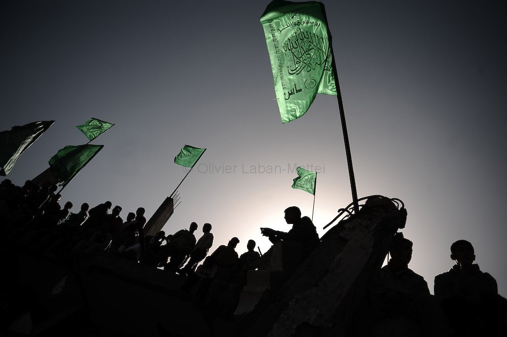 """Palestinian supporters of Hamas wave the movement's flags as they demonstrate on the rubble of a house in Gaza City on January 30, 2009. Palestinian president Mahmud Abbas said his Hamas rivals will """"never"""" be able to take over the West Bank as they did the Gaza Strip, where they ousted his forces in 2007."""
