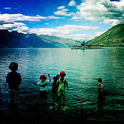 Children play on the fore shore as the TSS Earnslaw, the 100 year old vintage coal fired passenger steam ship which sails on Lake Wakatipu, Queenstown, New Zealand. The popular tourist attraction is celebrating it's centenary year with celebrations planned for October 2012.  Queenstown, Central Otago, New Zealand. 29th February 2012. Photo Tim Clayton