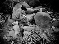 """Niño Picapedrero"" (child who digs out stones), sits for hours manually shatters rocks into gravel, without protective eyewear, adequate footware or training, to earn money for his family, Retalhuleu Province, Guatemala.  Guatemalan-American NGO CEIPA provides aid and education for underprivileged children such as these.    Poverty has been a major factor in the rise in child migrants embarking on the treacherous journey north to the United States.  The World Bank says over 90% of the indigenous population live below the poverty line."