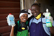 Jovita Masanyika and her husband holding some of the soap products that they make and sell.<br /> <br /> Jovita set up and now runs a soap making business selling a variety of soaps from shampoo to disinfectant.<br /> <br /> She attended MKUBWA enterprise training run by the Tanzania Gatsby Trust in partnership with The Cherie Blair Foundation for Women.