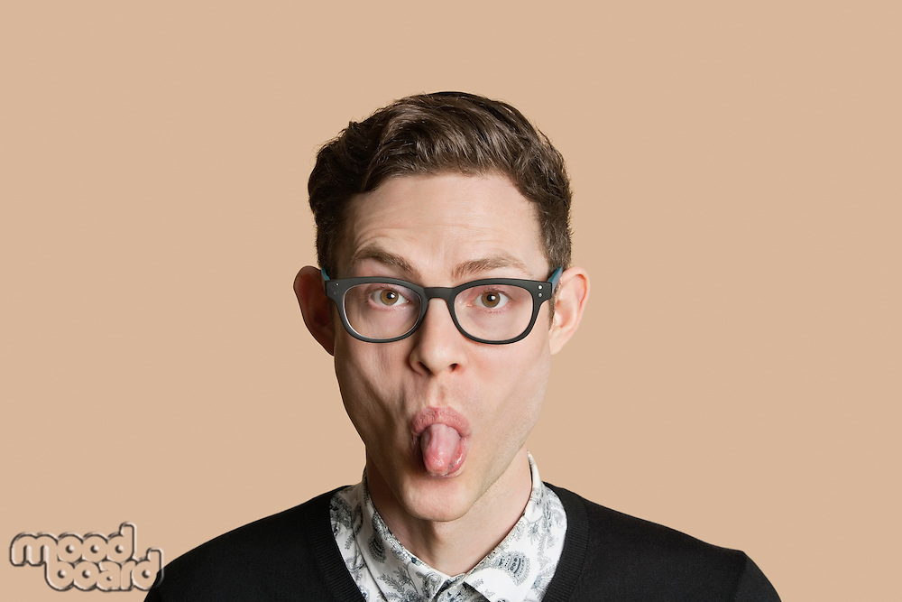 Portrait of a mid adult man sticking out tongue over colored background