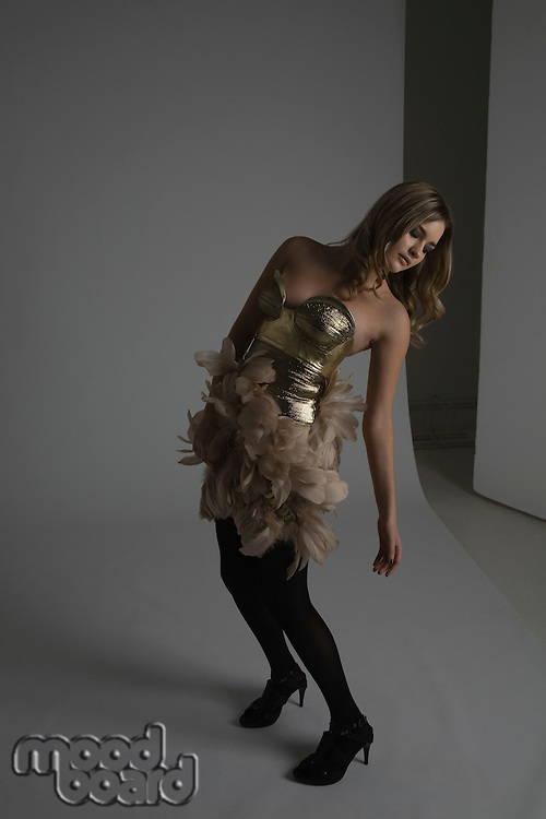 Fashion Model Modeling Gold Dress With Feathers