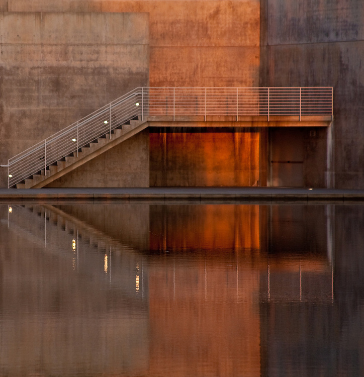 Stairs and landing lit by rising sun are reflected in water.