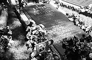 The grave of Elvis Presley on the grounds of his Graceland mansion. Flowers are layed on the thombstone each year to commemerate his death. Memphis, Tennessee, USA