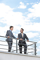 Businessmen standing at terrace railings against sky