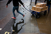 A delivery of boxes on a trolley, crossing over a puddle after rainfall in Oxford Street, central London.